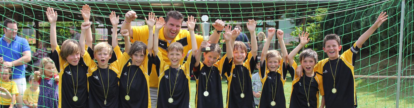 Spieler und Trainer unserer Fussball-Jugendmannschaft freuen sich auf Grund des gewonnenen Pokals beim Willi-Mark-Turnier.