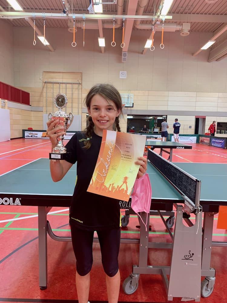Yola mit Pokal und Urkunde vor Tischtennisplatte